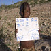 Himba Child Holding A Paper With Himba Words, Epupa, Namibia by Eric Lafforgue