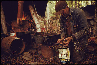 RESIDENT OF ROXBURY, VERMONT, DRAWS OFF THE FINISHED SYRUP FROM A HOMEMADE EVAPORATOR.