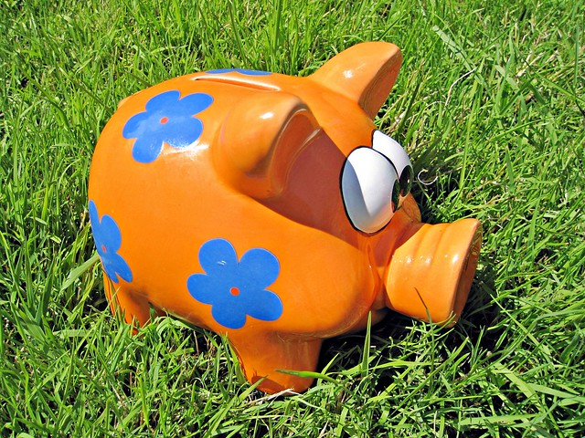 Orange piggy bank on grass