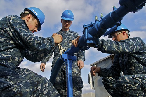 USS Bonhomme Sailors connect potable water to berthing and messing barge