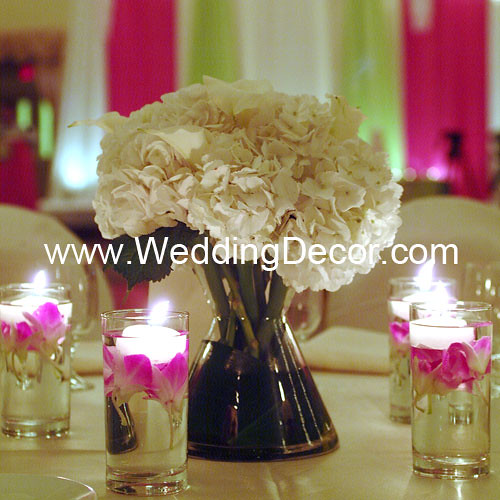 A wedding centerpiece in a small bow tie vase with hydrangeas calla lilies