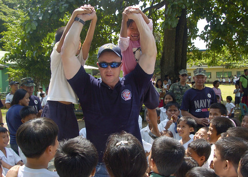 USS Howard Sailor lifts children at Tagburos Elementary School during a Cooperation Afloat Readiness and Training (CARAT) Philippines 2011 community service project