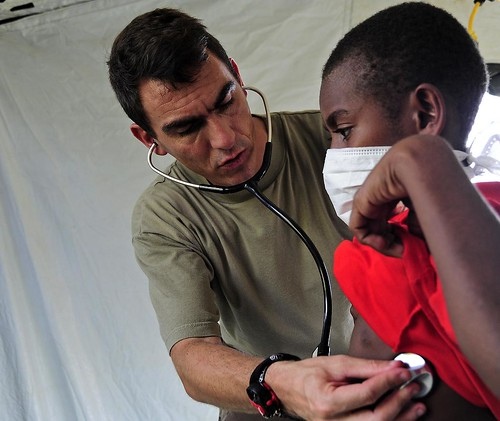 Doctor uses a stethoscope to examine a child