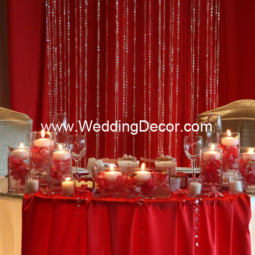 Head table decorations for a wedding reception in red and gold with floatin