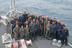 In this file photo, members of USS Guardian's (MCM 5) crew and the ship's guest riders from the Royal Australian Navy gather for a group picture on the ship's foc'sle April 8 while transiting from Singapore to Makassar, Indonesia. (U.S. Navy photo by Mineman Seaman Daniel Chaboya)