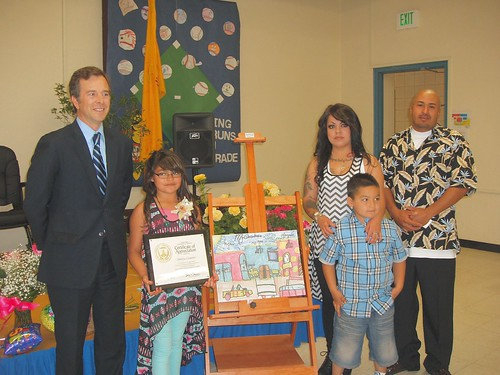 State Director Terry Brunner presents an award to Mireya Cisneros as her parents and her younger brother look on.