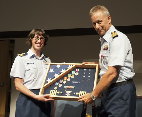 U.S. Coast Guard Lt. Judy Maisano and Capt. Richard Gaines display a shadowbox during a retirement ceremony held at the U.S. Coast Guard Academy in New London, Conn., June 15, 2012. Gaines received the shadowbox as a gift during his retirement to showcase his career in the Coast Guard. U.S. Coast Guard photograph by Petty Officer 3rd Class Diana Honings.