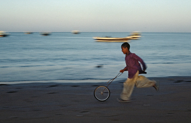 Boy Plays with Bicycle Wheel in Iran