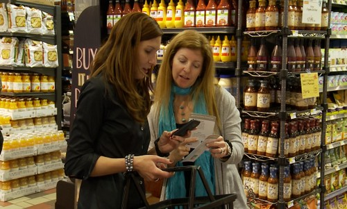 FSIS public affairs specialist Donna Karlsons demonstrates the Mobile Ask Karen food safety app to a shopper at Whole Foods Market in Logan Circle, Washington, D.C.