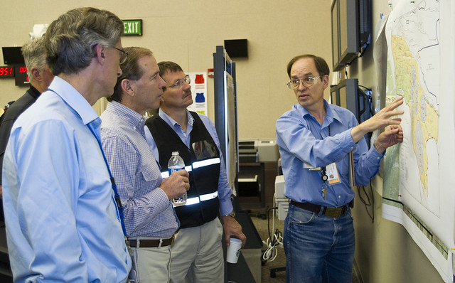 Sen. Tom Udall, second from left, and Charlie McMillan, at left, hear an update from a Los Alamos National Laboratory environmental specialist during a briefing on the Las Conchas Fire.  Photo by James Rickman.