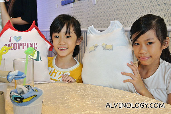 Two sisters showing off their tee-shirt pillows