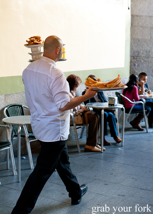 Waiter carrying loaded trays of Spanish hot chocolates and churros at Chocolateria San Gines in Madrid, Spain
