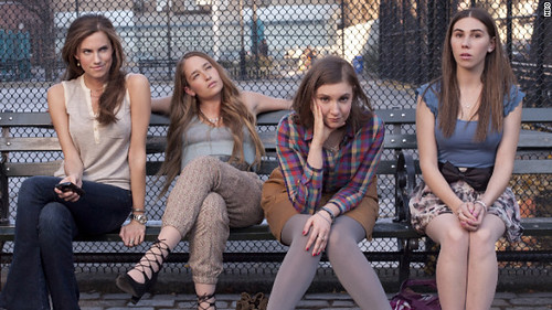 the four women who star in GIRLS, sitting on a park bench together