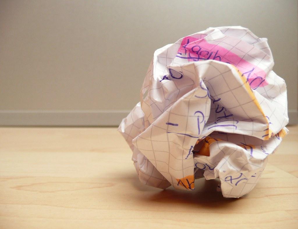 overcoming writer's block - crumpled paper on wooden floor - crushed paper