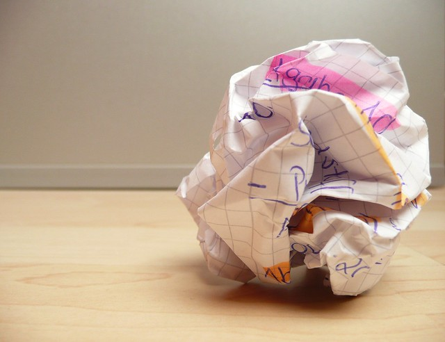 overcoming writer's block - crumpled paper on wooden floor - crushed paper