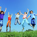 Group of five happy children jumping outdoors. by Lighttruth