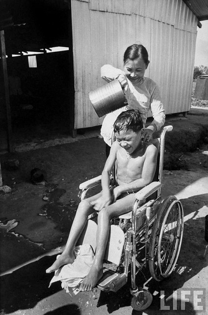 A 10-year-old paraplegic Lau Nguyen, wounded during the Vietnam War returning home after 3 years of medical treatment in the US, by Larry Burrows 1970