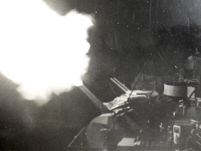 THE PACIFIC WAR: Looking aft, HMAS SHROPSHIRE's starboard 4-inch battery night firing. Collection of Alan Meade, RAN 1943-1946.