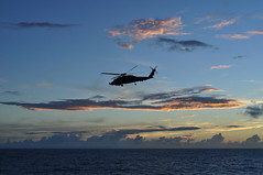 PACIFIC OCEAN (March 3, 2011) A helicopter from Helicopter Anti-Submarine Squadron Light (HSL) 43 on board USS Preble (DDG 88) departs as sunrise to begin a day of search and surveillance operations as part of Preble's Economic Exclusion Zone (EEZ) mission in the Western Pacific. (U.S. Navy photo taken by Lt. j.g. Anna Barcus/Released)