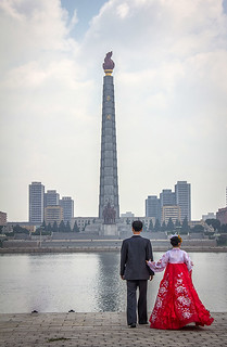 Young couple watching the Juche Tower from the bank of the river, Pyongyang, North Korea