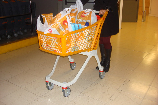 Orange shopping trolley filled with goods and pushed by lady.