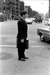 John Cage standing on curb in dark suit, holding briefcase, by William Gedney 1967