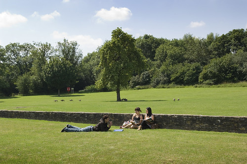 Students relaxing on area of grass outside the Farm House on Frenchay Campus.