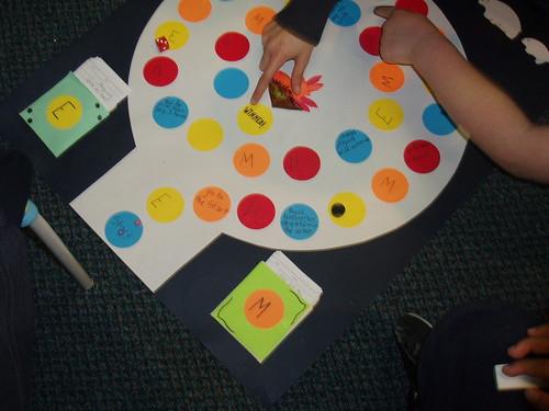 gioco da tavolo poggiato per terra con mani che indicano il tabellone