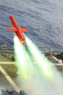 A red drone missile is launched from the deck of a Navy vessel.