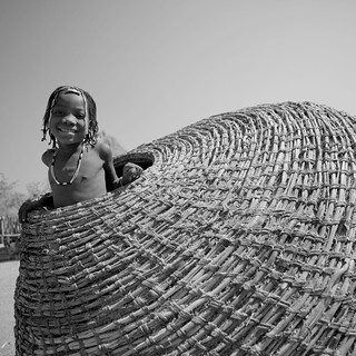 Mudimba tribe kid in a giant basket - Angola