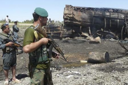 Pro-US Afghanistan puppet military forces stand next to burned-out fuel tankers that were liberated and destroyed by the resistance fighters struggling to oust the American and NATO occupation forces from their country. Attacks occur everyday. by Pan-African News Wire File Photos