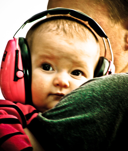 A baby wears large headphones while listening to music
