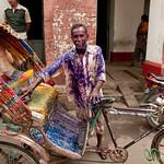 A Rickshaw Drives Through Holi Celebrations - Dhaka, Bangladesh