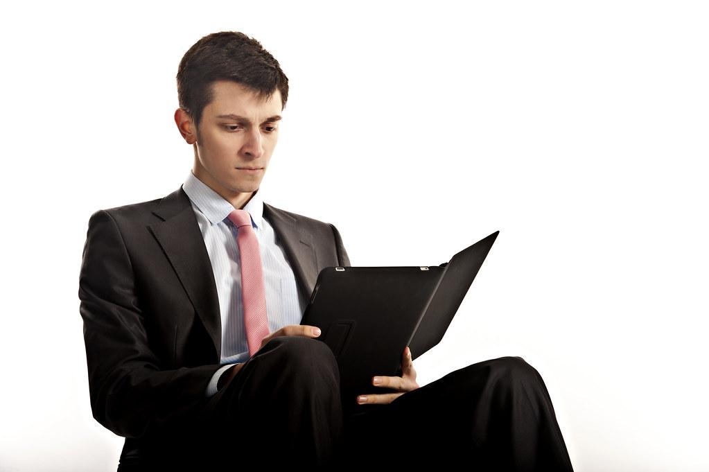 Businessman seated and reading iPad