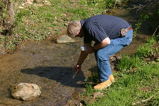 Rick Handshoe using a conductivity meter in a creek.