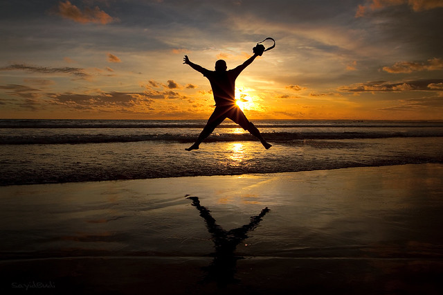 A photographer jumping for joy during sunset - How to be a Happy Photographer