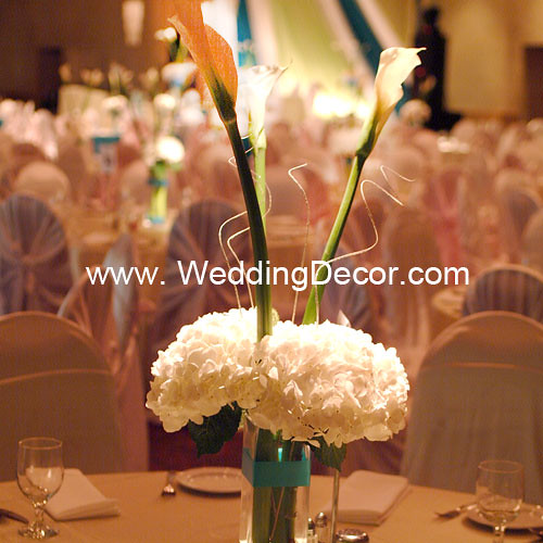 A wedding centerpiece with hydrangea flowers and calla lilies in a small