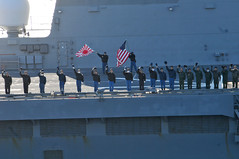 In this file photo, sailors aboard the Japan Maritime Self-Defense Force helicopter destroyer JDS Hyuga (DDH 181) wave the American and Japanese flags April 4 as a sign of friendship during a pass and review with the aircraft carrier USS Ronald Reagan (CVN 76). (U.S. Navy photo by Mass Communication Specialist Seaman Nicholas A. Groesch)