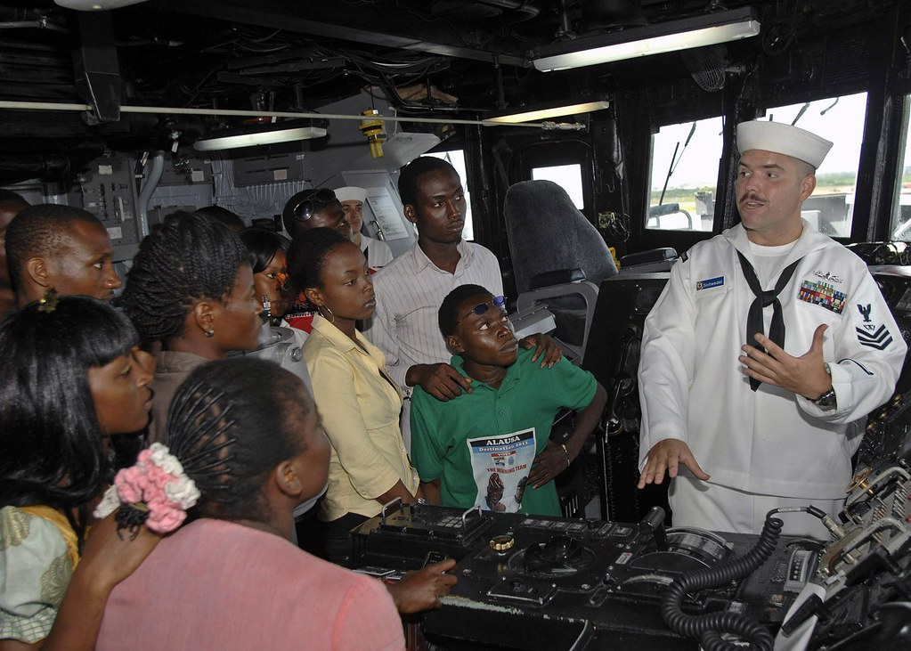 Sailor explains the function of the ships helm to Nigerian NGO workers.