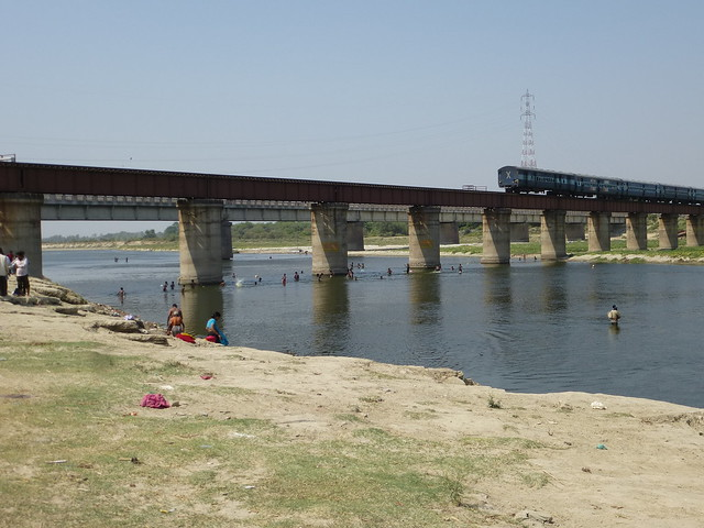A view of the river with assorted people and the rail bridge straddling it