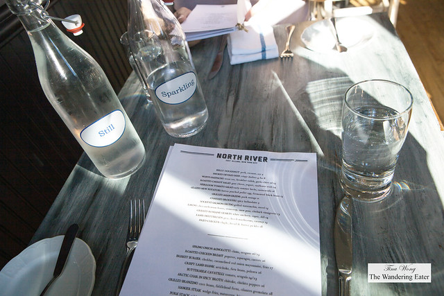 Table setting, menu and bottles of gratis still and sparkling water