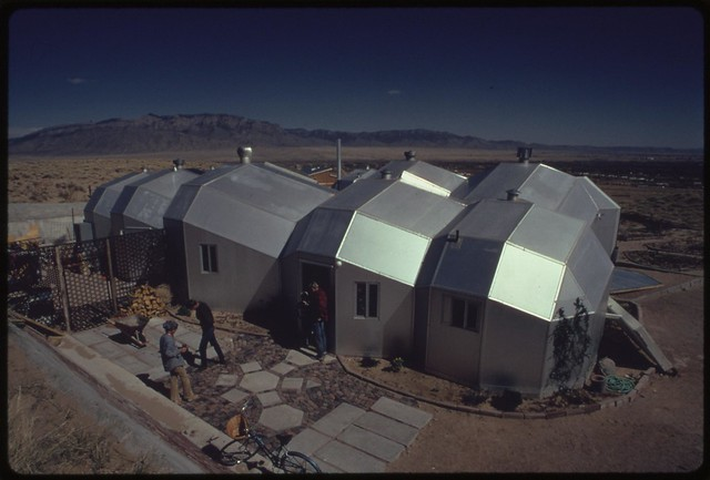 Zome house using solar heating built near Corrales, New Mexico. The modular interconnected units are hexagon shaped with polyhedra roofs. Aluminum construction has an inner core of urethane foam for insulating efficiency. Glass walls covered at night pass sunlight to heat blackened 55-gallon drums filled with water, 04/1974 Documerica by Boyd Norton.