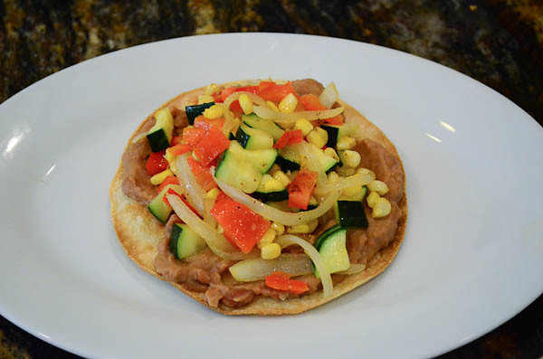 A toasted tortilla covered with refried beans and cooked vegetables.