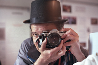 reflected self-portrait with Canon AE-1 camera and workhouse hat