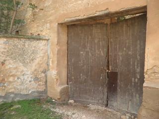 Puerta que protege el recinto del Monasterio de los posibles vándalos, aunque el tiempo y la desidia están campando a sus anchas.