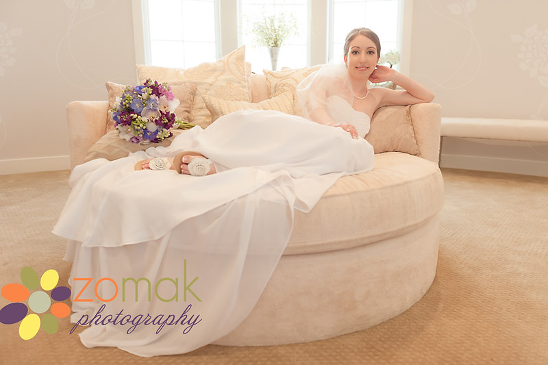 Beautiful bride poses on a sofa before her destination wedding in Maui at the Sugar Beach Events Building
