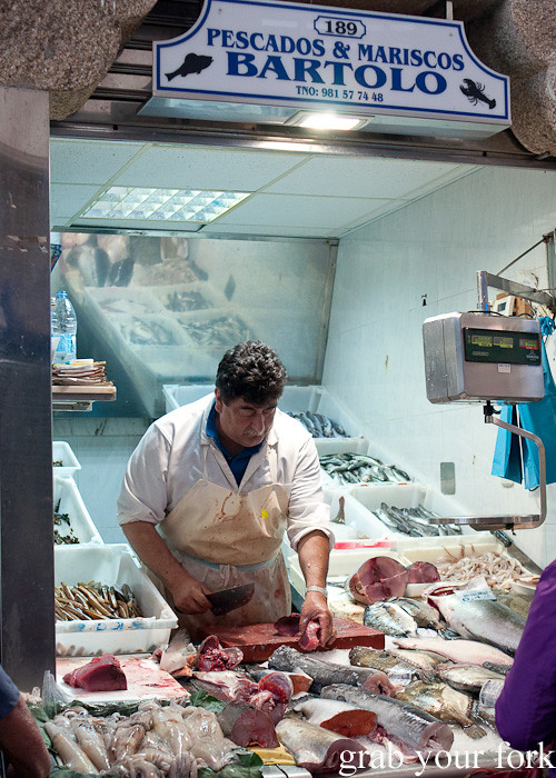 Fishmonger with curved machete at Mercado de Abastos farmers market in Santiago de Compostela, Spain