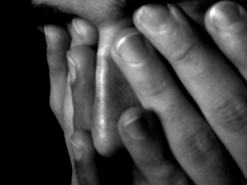 A tired person holding their face in their hands