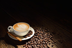 Cup of cafe latte and coffee beans on old wooden b…