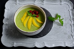 Green smoothie bowl with mango and raspberries